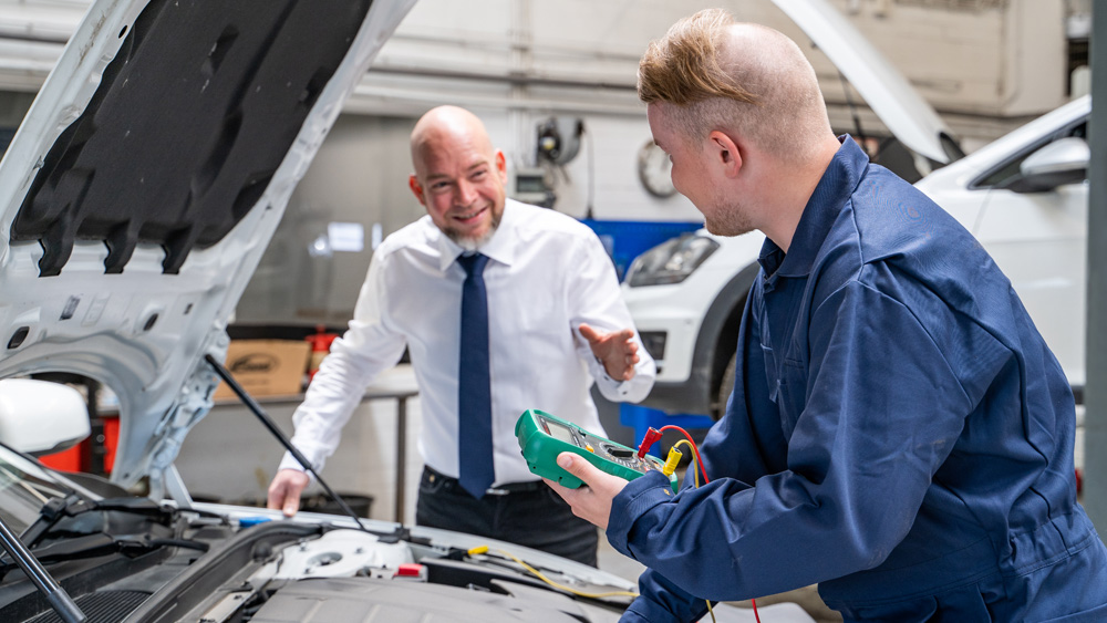 Car repair shop manager discussing Training plans with mechanic or technician holding a multimeter perform electrical measurements on a car