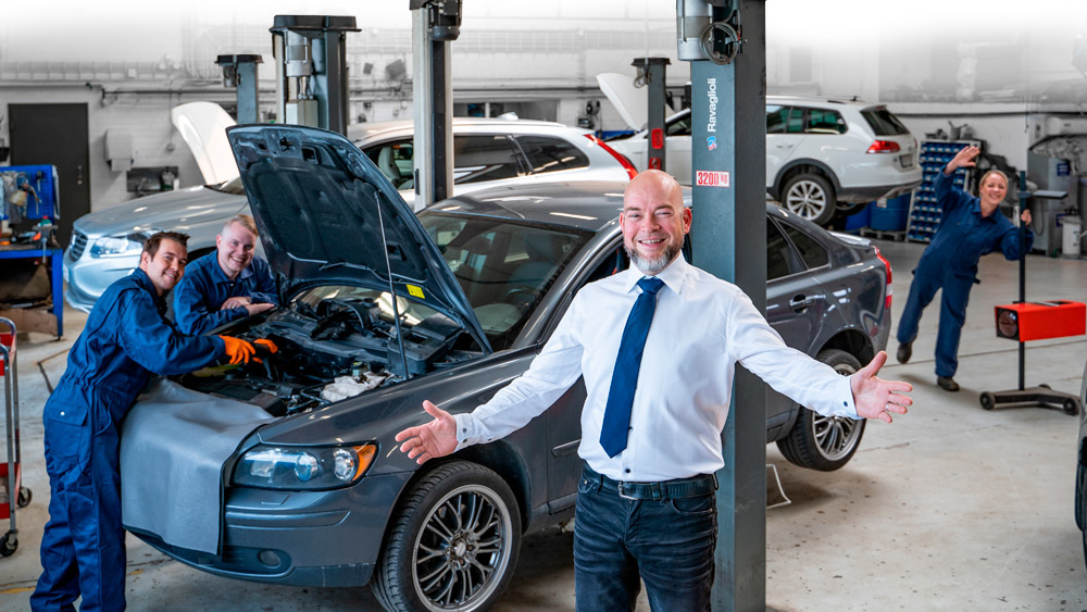 Happy car repair shop manager spreading his hand in front of his mechanics who are satisfied with Prodiags
