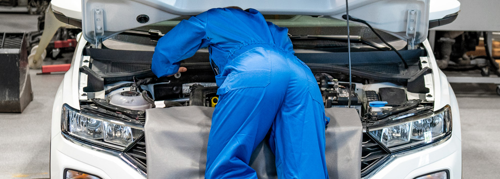 Mechanic bending over engine