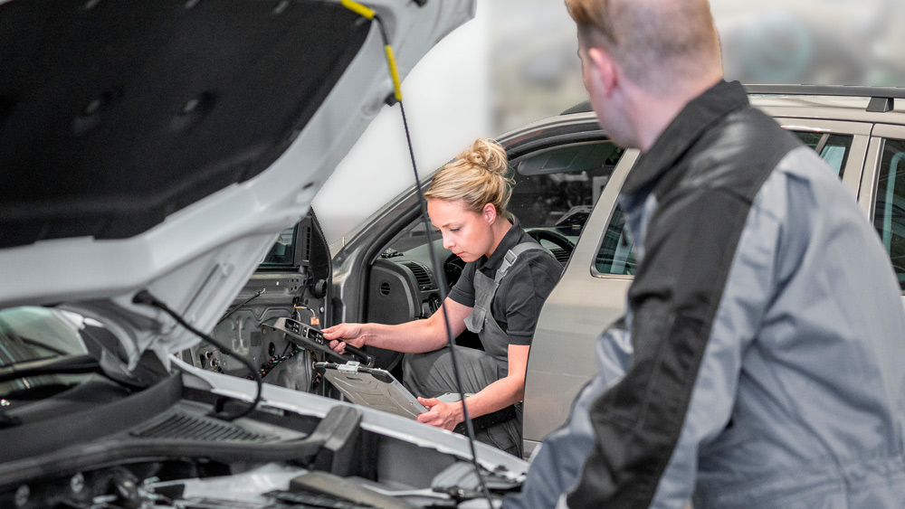 Male mechanic looking at the female technician that learned automotive electrics with Prodiags Online Training with envy