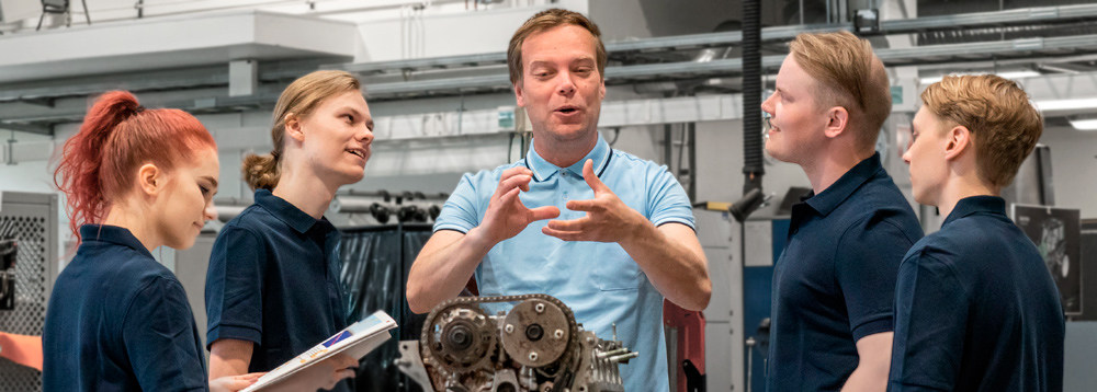 Automotive trainer with students around car engine