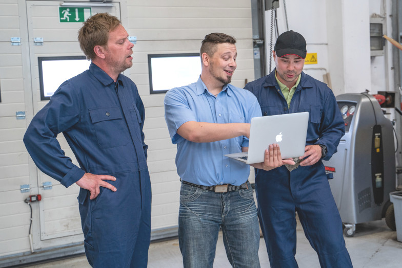 Car Repair Shop Manager and Mechanics Going Through Training Module Results Together