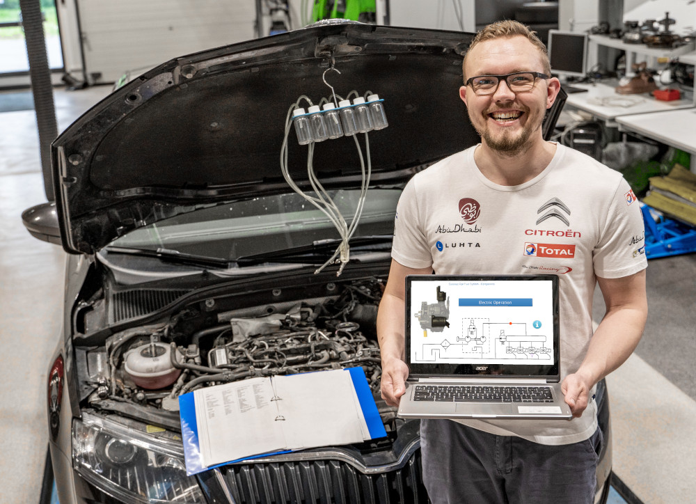 Automotive teacher by car showing Prodiags Training module on computer
