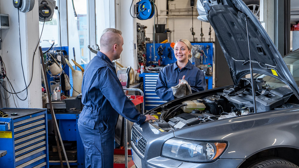 Happy mechanics standing by a car in the car repair shop, putting to use what they learned from the Prodiags Automotive Training