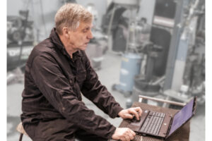 Old and experienced mechanic or technician sitting by his laptop in the auto repair shop studying with prodiags pre-learning training concept for car workshops and automotive garages.