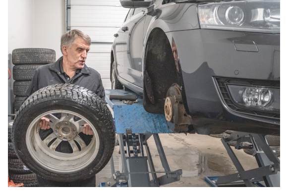 Experienced middle-aged or old mechanic with gray hair lifting a car tyre for mounting the tire. Dark gray car on scissor lift. Representing a user of the Prodiags Online Pre-Learning Training concept for automotive workshops.