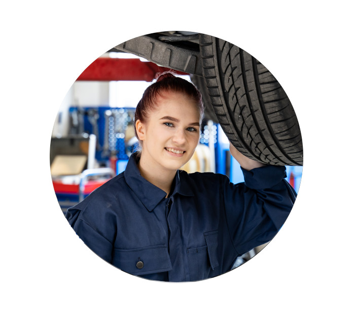 Young female car mechanic or auto technician with red hair in automotive workshop or garage under a car, van, truck or lorry.