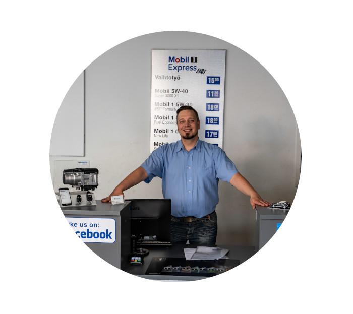 Workshop manager behind service register or desk in auto workshop or repairshop. Blue shirt, brown hair and beard.