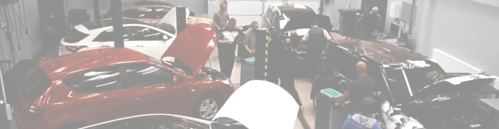 Image from TRaining Event for automotive technicians or car mechanics. In the picture different cars, people and some diagnostic equipment in a workshop, garage, repairshop or training facility.